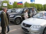 Народ привлекает серебристый Ниссан, стоящий рядом с УАЗами